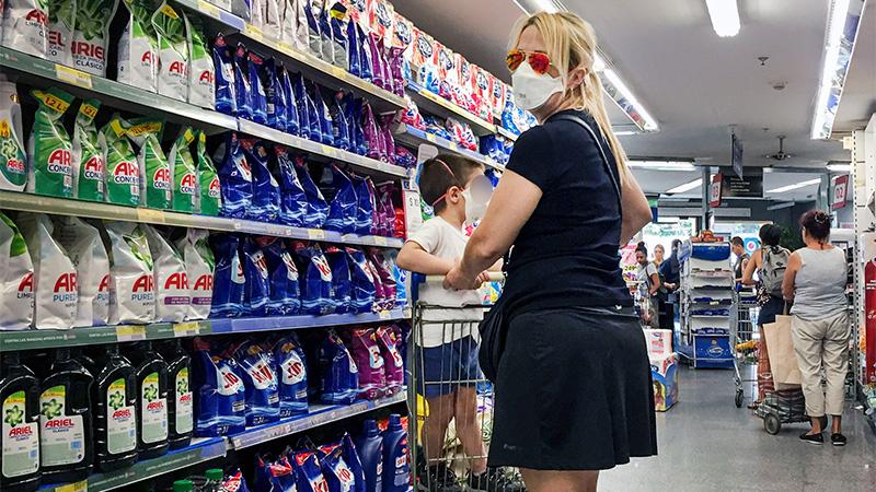Una mujer realiza compras en un supermercado con un niño.