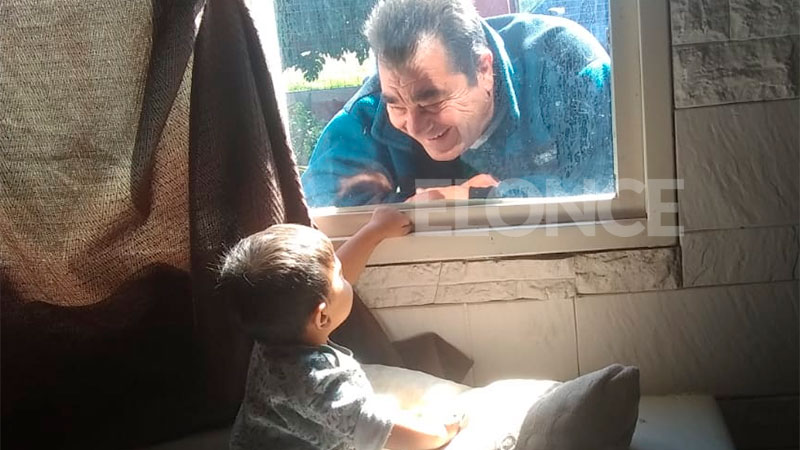Tierna foto: La visita de un abuelo a su nieto de un año a través de la ventana