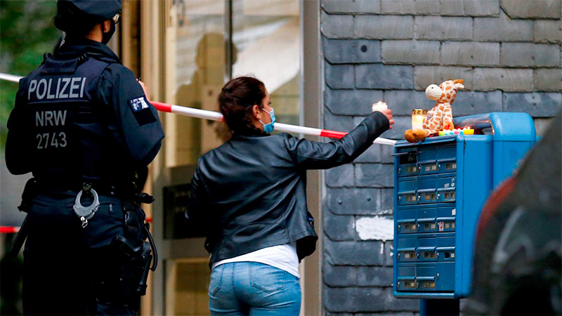 Una mujer prende una vela en la puerta del edificio.