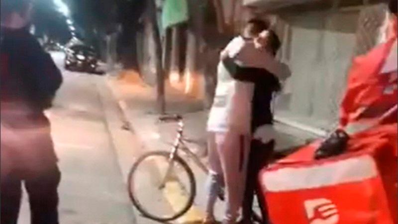 El abrazo del repartidor y la joven que lo ayudó.