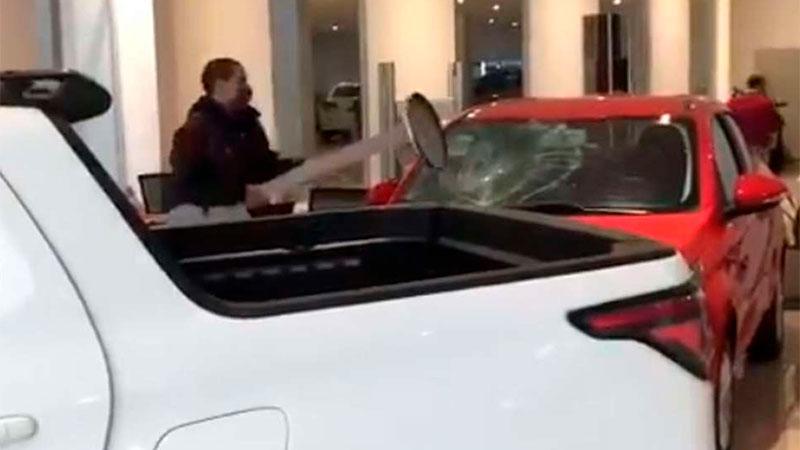 Enfurecido, un hombre destroza un auto en concesionaria.